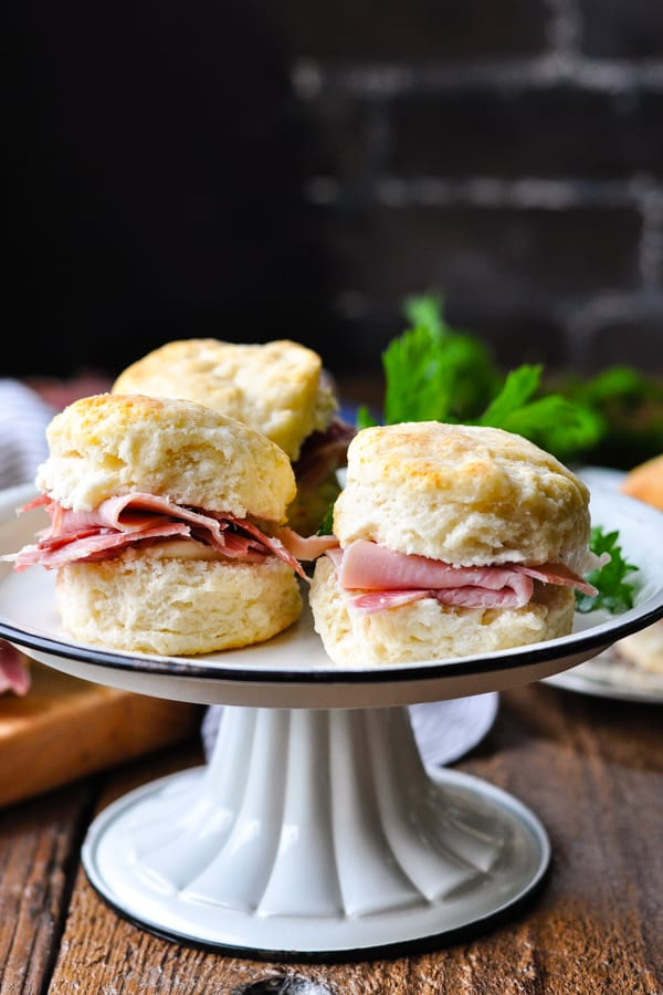 Front shot of a tray of ham biscuits in front of a dark background