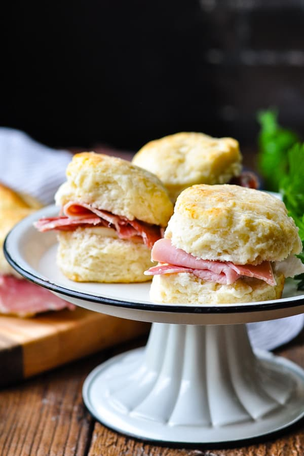 Tray of cocktail ham biscuits on a wooden table