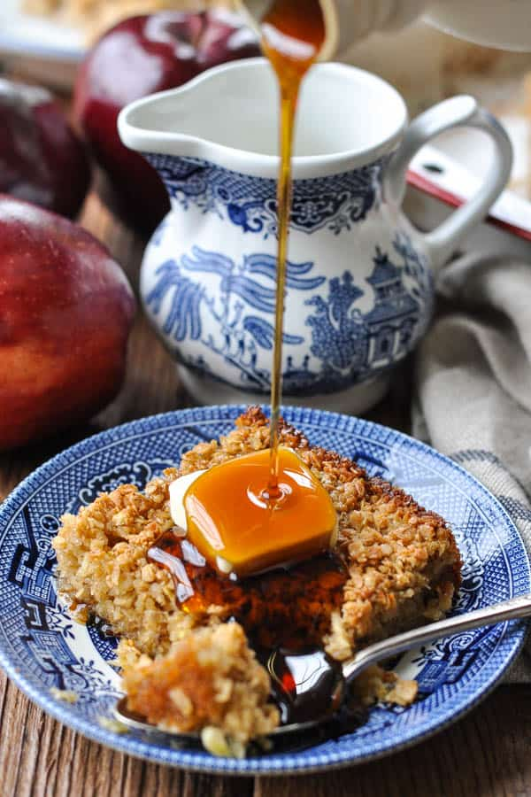 Pouring maple syrup on top of baked oatmeal with apples