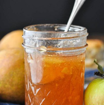 Jar of spiced pear jam with apples on a wooden table