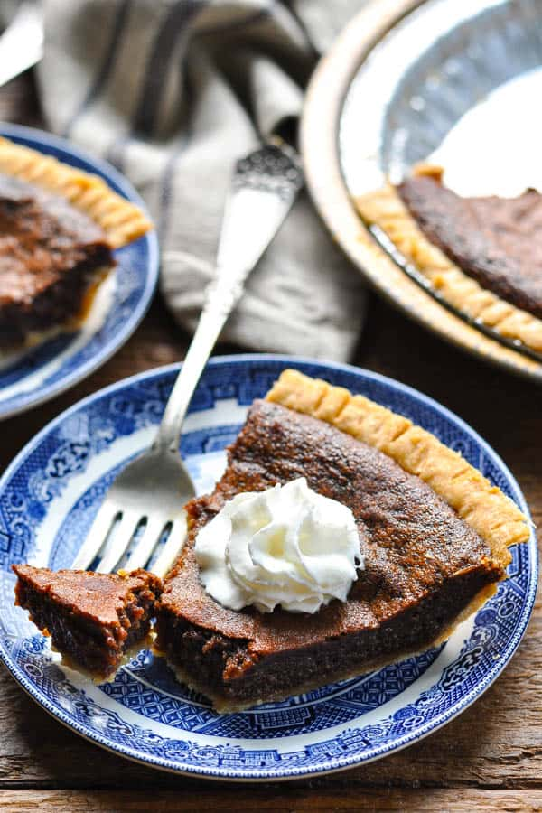 Bite of the best chocolate chess pie on a fork with pie in background