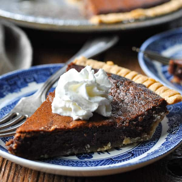 Square image of easy chocolate chess pie recipe on a blue and white plate