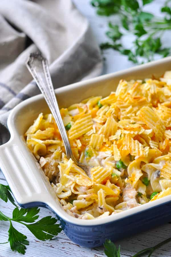 Front shot of cheesy tuna noodle casserole in a baking dish with a silver serving spoon