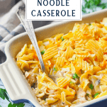 Side shot of a blue dish full of campbells tuna noodle casserole with a text title box at the top