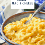 Creamy baked mac and cheese recipe served in a blue bowl with text title box at top