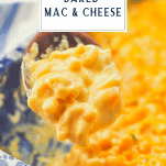 Close up shot of a spoonful of creamy baked macaroni and cheese with text title box over top
