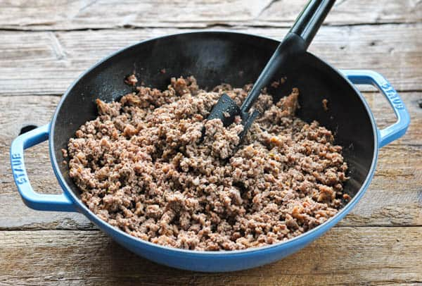 Ground beef and Italian sausage cooked in a cast iron skillet