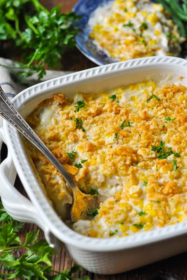 Spoon in a pan of Amish Chicken Casserole with Corn and Ritz cracker crumb topping