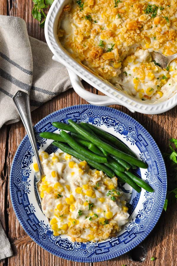 Overhead image of a plate of Easy Chicken Casserole on a wooden table with a side of green beans