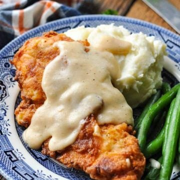 Front shot of crispy pan fried chicken cutlets on a plate with mashed potatoes and gravy
