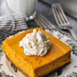 Pumpkin cheesecake bars with a graham cracker crust and a dollop of whipped cream sitting on a brown and white plate