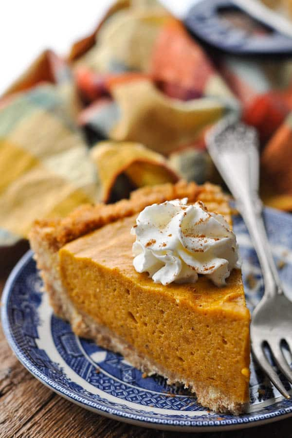 Front shot of a slice of pumpkin chiffon pie with a plaid napkin in the background