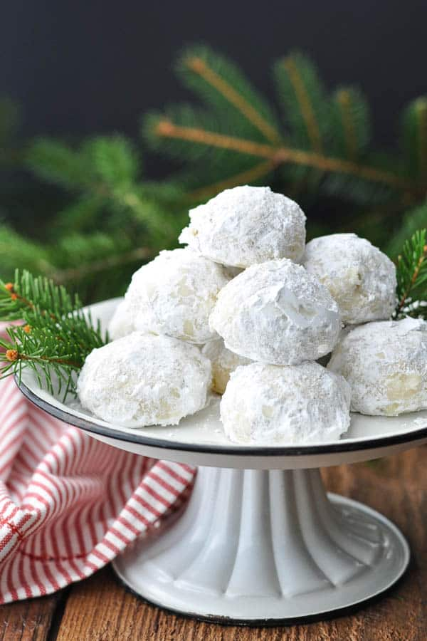Front shot of Russian Tea Cakes on a cake stand in front of a dark backdrop
