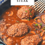 Homemade Salisbury Steak in a skillet with text title box at the top