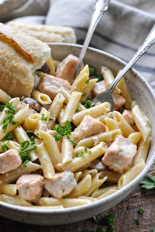 Close up side shot of a bowl of creamy salmon pasta with fresh parsley on top
