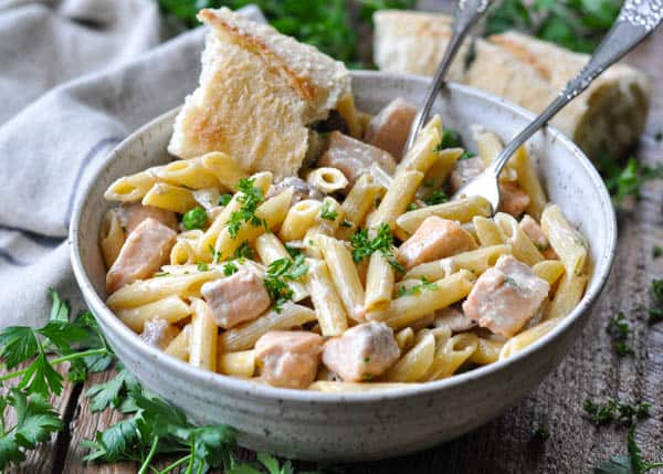 French baguette served with a big bowl of easy salmon pasta