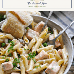 Bowl of salmon pasta with mushrooms and peas in a bowl with text title box at the top