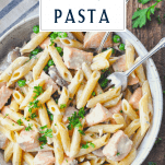 Overhead image of creamy salmon pasta recipe with a text title box at the top