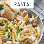 Salmon pasta with cream sauce in a bowl with a text title box at the top