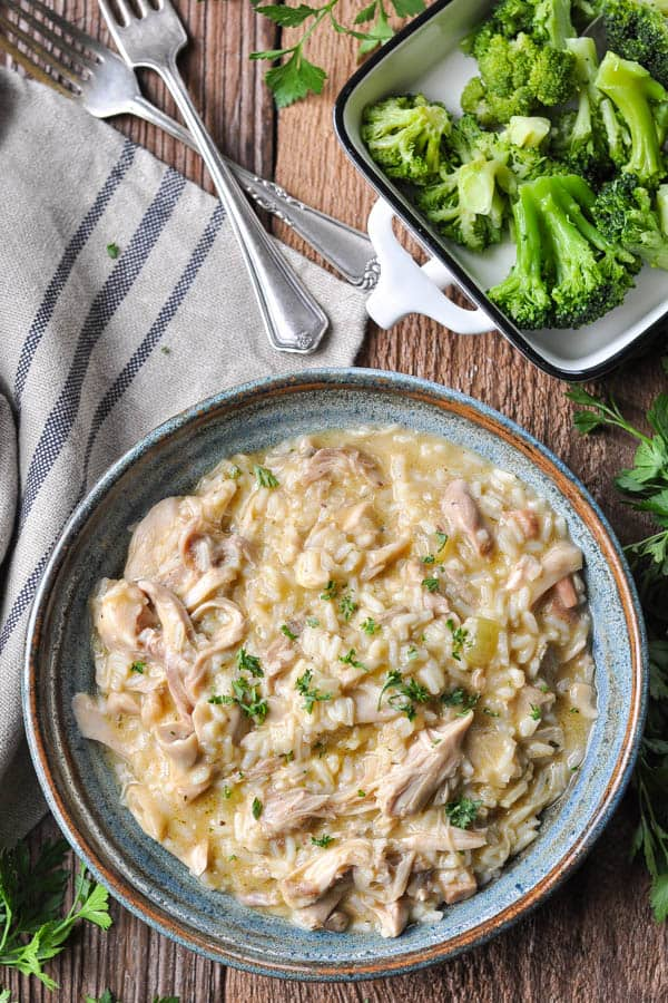 Overhead image of a bowl of slow cooker chicken and rice served with a side of broccoli