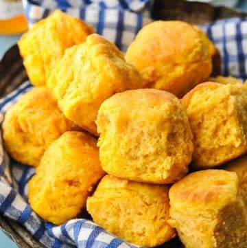 Close up shot of sweet potato biscuits in a serving dish with honey in the background