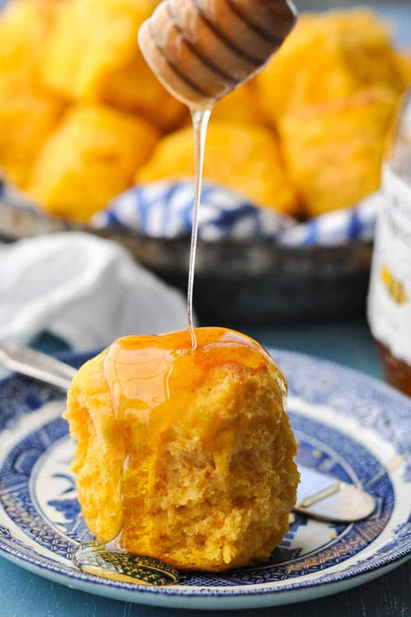 Close up shot of drizzling honey on top of a buttermilk sweet potato biscuit
