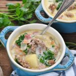 Side shot of a spoon in a bowl of zuppa toscana soup