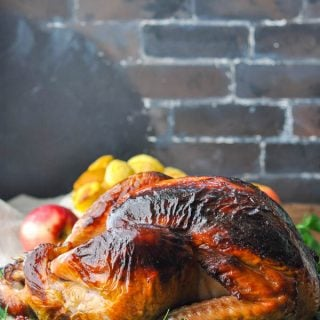 A beautiful roasted turkey flavored with an apple cider turkey brine on a platter in front of a dark brick wall