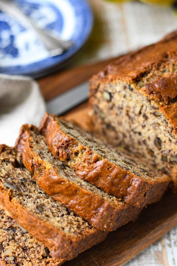 Loaf of the best banana nut bread sliced on a cutting board