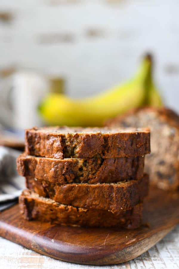 Front shot of four slices of banana nut bread stacked on a wooden cutting board