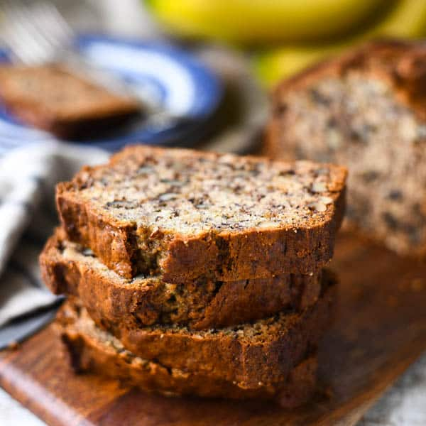 Square image of slices of easy banana nut bread on a wooden cutting board