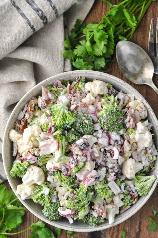 Long overhead image of a bowl of broccoli cauliflower salad on a wooden table