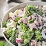 Front shot of raw broccoli and cauliflower salad recipe in a white bowl with striped towel in the background