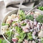A homemade broccoli and cauliflower salad recipe served in a handmade white ceramic bowl