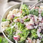 Close up side shot of a big serving bowl full of the best broccoli cauliflower salad recipe