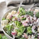 Two silver serving spoons in a bowl of raw broccoli and cauliflower salad with bacon