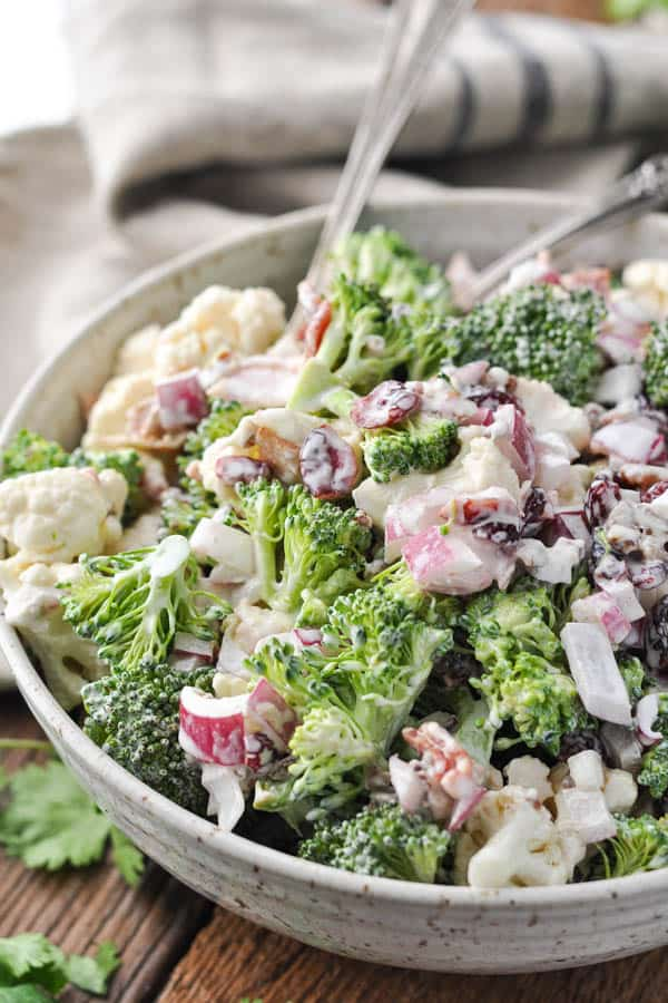 Close up front shot of an easy broccoli cauliflower salad recipe in a serving bowl