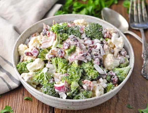 Horizontal shot of a bowl of Amish Broccoli Cauliflower Salad with bacon