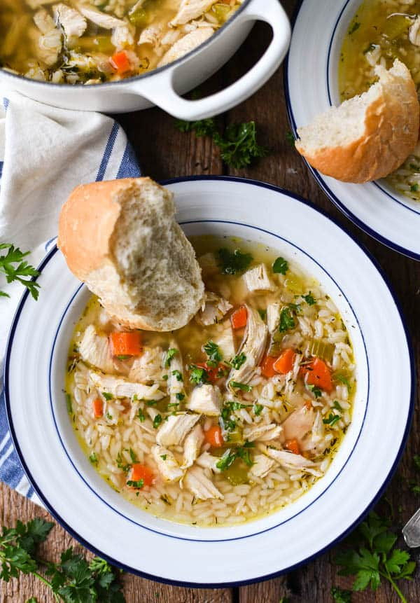 Close overhead image of a bowl of chicken and rice soup with a side of bread