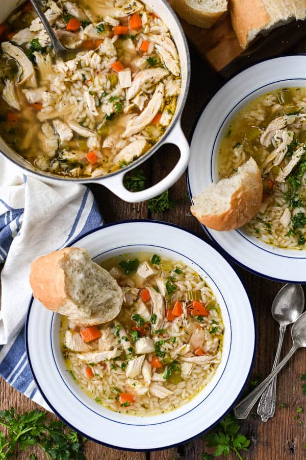 Overhead shot of two bowls of homemade chicken and rice soup on a wooden table with bread