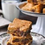 Three easy chocolate chip cookie bars on a plate with milk in the background