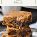 Close up shot of a stack of chewy chocolate chip cookie bars with a text title box at the top
