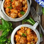 A meatball and pasta casserole served in two white bowls with fresh basil nearby