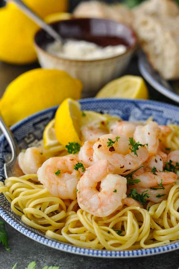 Close side shot of easy shrimp scampi in a bowl with pasta and lemon