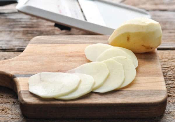 Thinly sliced potatoes on a cutting board