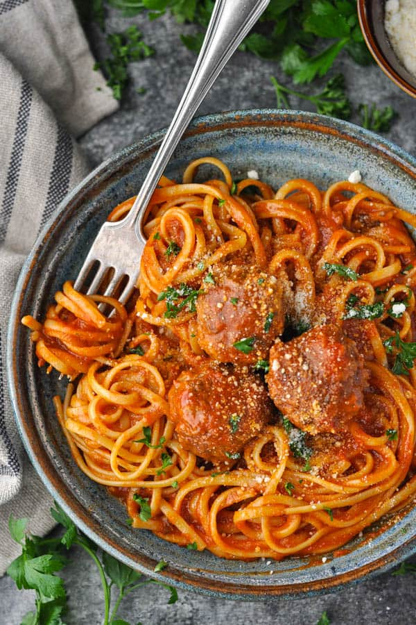 Close overhead image of Italian meatballs with pasta and herbs