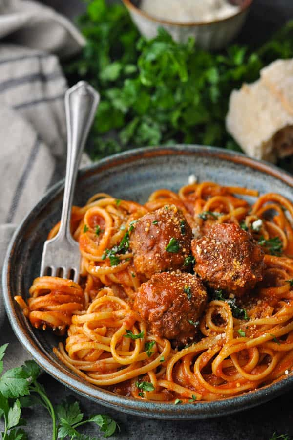 Easy homemade meatballs served in a blue bowl with plenty of spaghetti