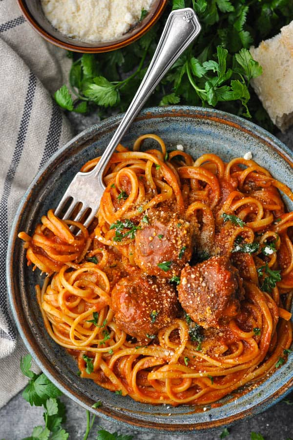 Overhead shot of a bowl of spaghetti and meatballs with fresh parsley and bread