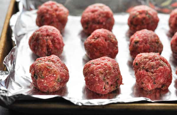 Raw meatballs on a baking sheet