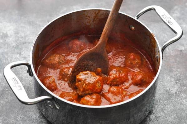 Meatballs simmering in marinara sauce